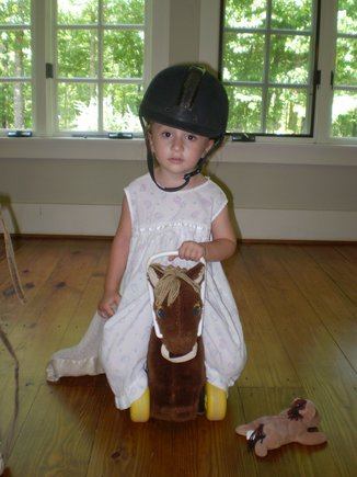"Cameron riding her pony with her LittleGiraffe ""thumby."""