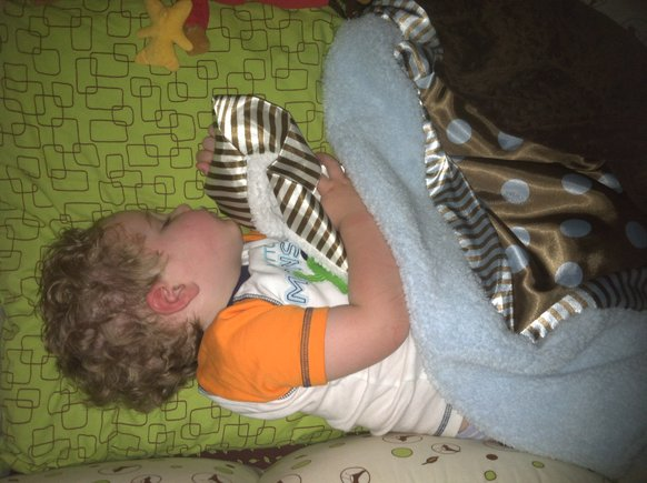 "Parker sleeping with his ""bank bank!"" We could not live without these blankies! We love them!"
